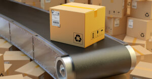 Cardboard box on conveyor belt in warehouse storage interior with stack of parcels