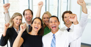 Portrait Of Business Team In Office Celebrating Looking At Camera Cheering